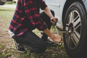 chica cambiando una rueda del coche